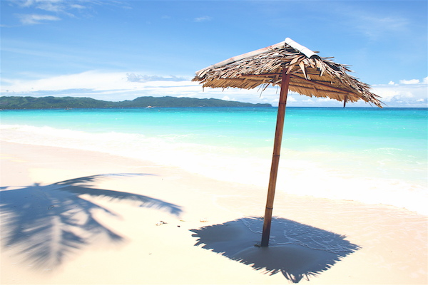 Picture of a sunny beach with a lonely umbrella