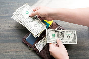 Picture of a hand picking dollar bills from wallet, to illustrate the lesson about Banking Vocabulary in Spanish
